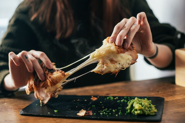Vrouw met tatoeages op vingers breekt klaar om croissant met gesmolten kaas en ham te eten