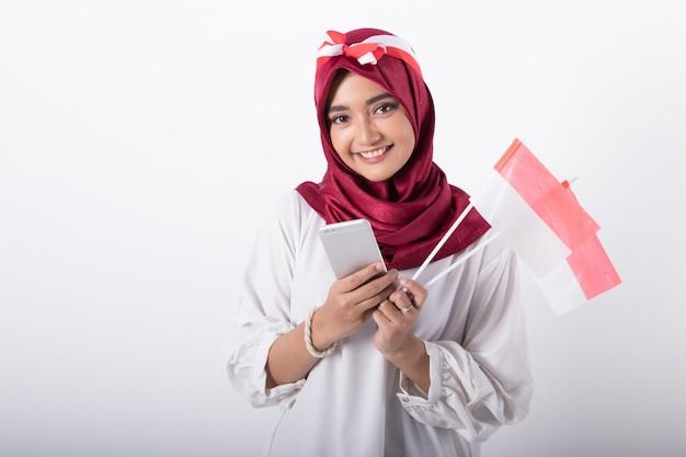 Vrouw met telefoon bij de indonesische viering van de onafhankelijkheidsdag