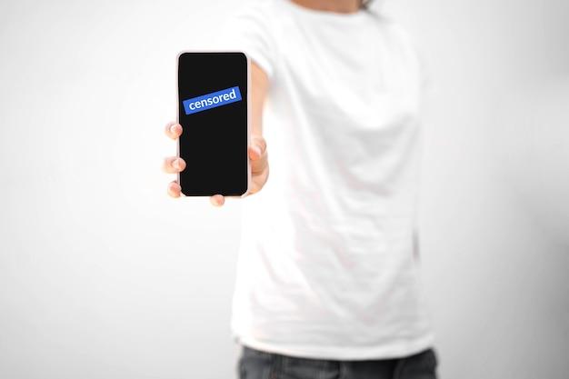 Vrouw met telefoon en gecensureerde tekst erop