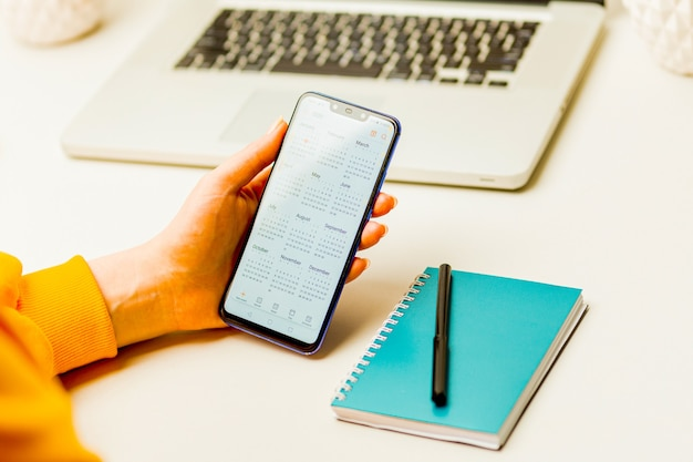 Vrouw met telefoon en kalender gebruiken om haar plan in het notitieblok te maken.