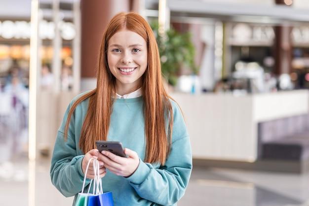 Vrouw met telefoon en kijken naar fotograaf