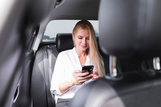Vrouw met telefoon in auto achterbank