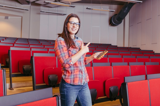 Vrouw met telefoon in universitair amfitheater