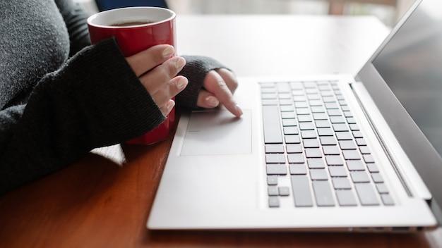 Vrouw met thee en binge kijken naar haar favoriete tv-series op laptop film downloaden en streamen movie