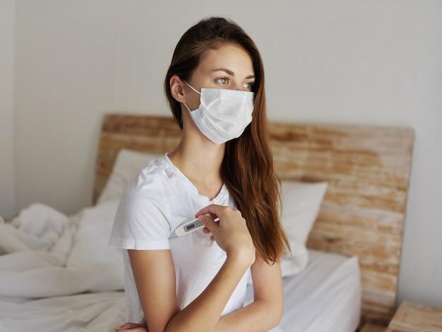 Vrouw met thermometer onder haar arm die een medisch masker draagt dat de temperatuur controleert
