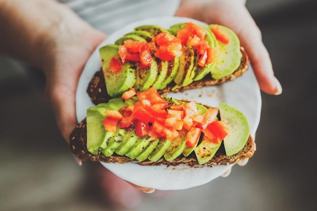 Vrouw met toast met avocado en tomaten op plaat.