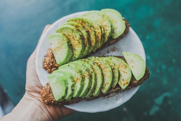 Vrouw met toast met avocado op plaat.