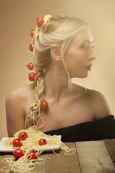 Vrouw met tomaten en spaghettis in haar haar