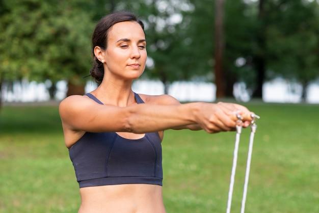 Vrouw met touwtjespringen en gesloten ogen
