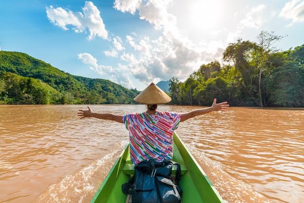 Vrouw met traditionele hoed die op het bruine water van de nam ou-rivier in laos kruist