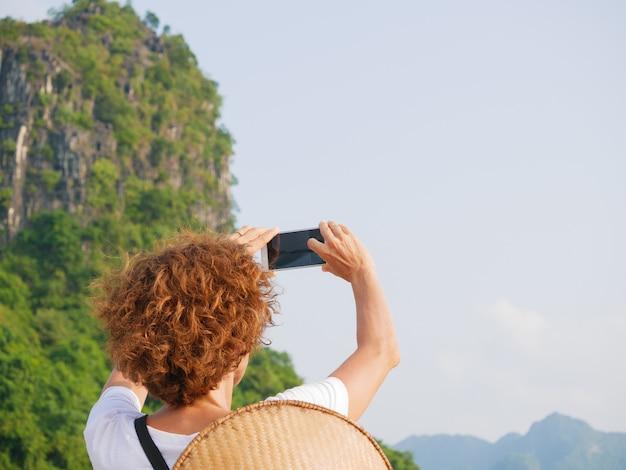 Vrouw met traditionele hoed die telefoon met behulp van in halong bay vietnam