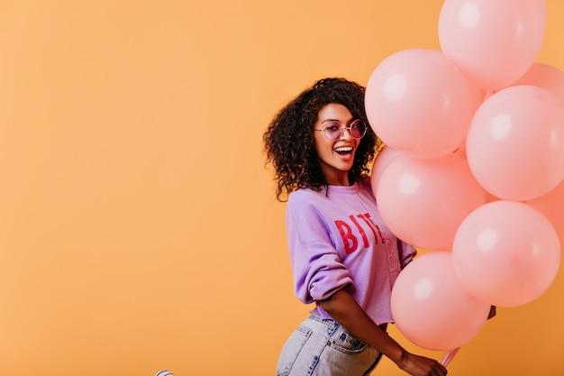 Vrouw met trendy kapsel poseren op oranje afterparty. lachen mooie zwarte meisje met ballonnen.