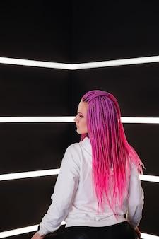 Vrouw met trendy roze vlechten in wit licht. draagbaar virtueel augmented reality digitaal innovatietechnologieconcept