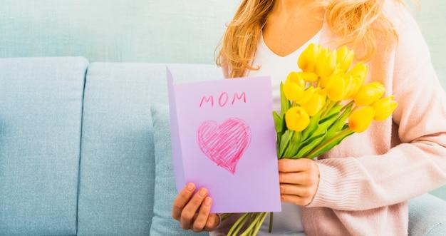 Vrouw met tulpen en prentbriefkaar voor moeder` s dag
