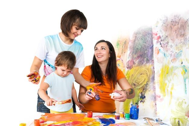 Vrouw met twee baby's schilderen met verf en borstels zittend aan kindertafel, kleurrijk oppervlak