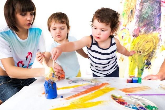 Vrouw met twee baby's schilderen met verf en borstels zittend aan kindertafel, kleurrijke achtergrond