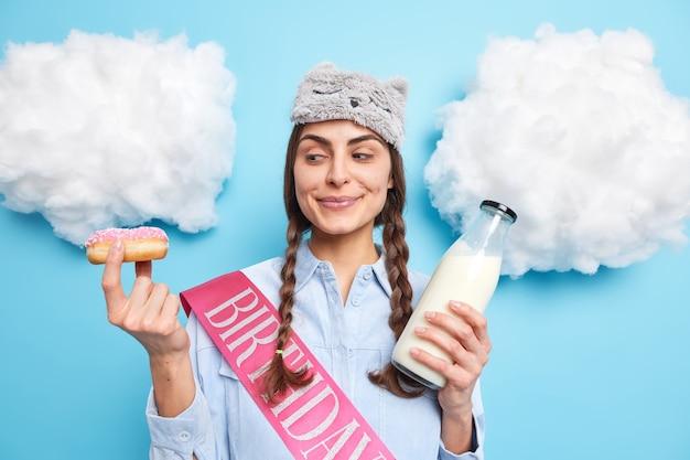 Vrouw met twee staartjes kijkt naar smakelijke geglazuurde donut die het gaat eten met verse melk houdt van zoete heerlijke desserts draagt huishoudelijke kleding geïsoleerd op blauw
