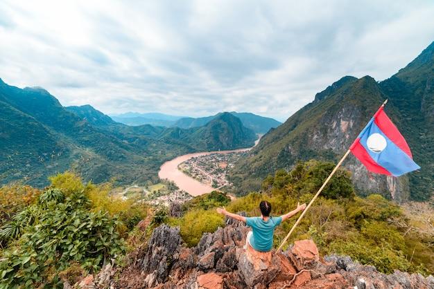 Vrouw met uitgestrekte armen veroverende bergtop op nong khiaw nam ou riviervallei laos volwassen mensen reizen millenials concept reisbestemming in zuidoost-azië