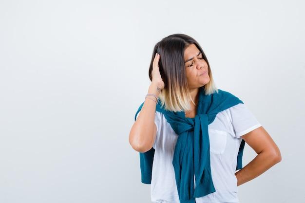Vrouw met vastgebonden trui die de hand op het hoofd houdt in een wit t-shirt en er peinzend uitziet. vooraanzicht.