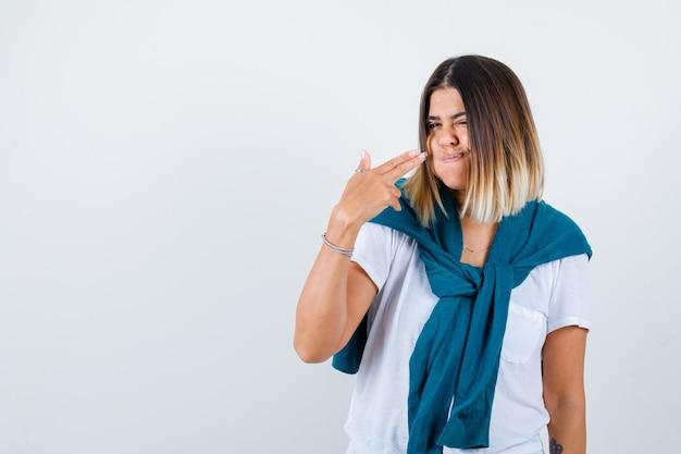 Vrouw met vastgebonden trui die een pistoolgebaar toont, wangen blaast in een wit t-shirt en er zelfverzekerd uitziet. vooraanzicht.