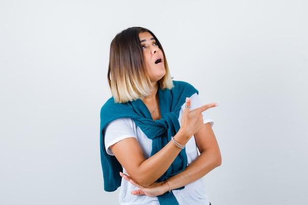 Vrouw met vastgebonden trui naar rechts wijzend, omhoog kijkend in wit t-shirt en verwonderd kijkend. vooraanzicht.