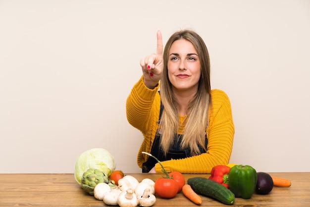 Vrouw met veel groenten die op het transparante scherm betrekking hebben