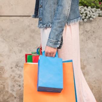 Vrouw met veel heldere boodschappentassen