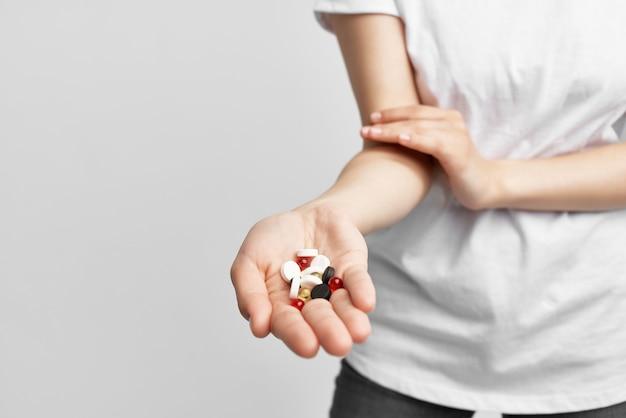 Vrouw met veelkleurige pillen in de geneeskunde van de palmapotheek