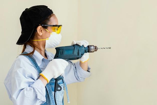 Vrouw met veiligheidsbescherming apparatuur werken