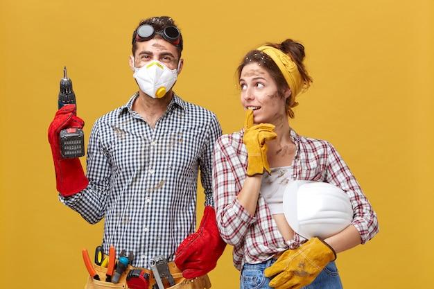 Vrouw met veiligheidshelm die aandachtig kijkt naar haar echtgenoot die bouwvakker is en hem vraagt om iets in huis te repareren. jonge ingenieur met boormachine en riem van gereedschappen