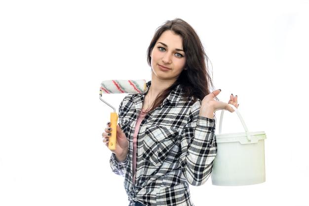 Vrouw met verf in emmer en hulpmiddelen op wit wordt geïsoleerd dat