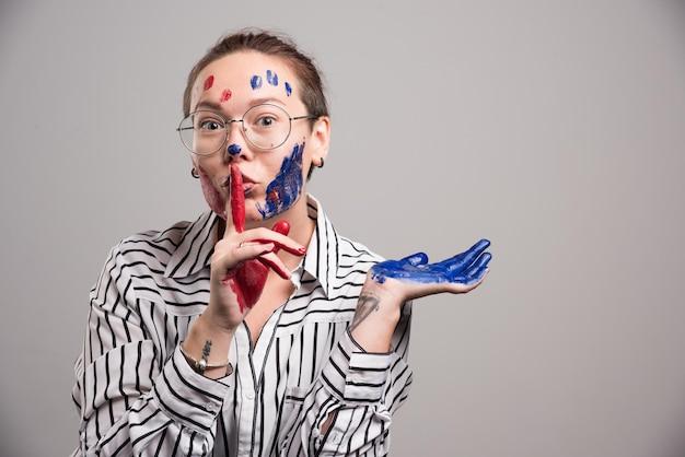 Vrouw met verf op haar gezicht en bril op grijs