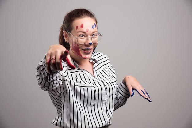 Vrouw met verf op haar gezicht en glazen op grijze achtergrond