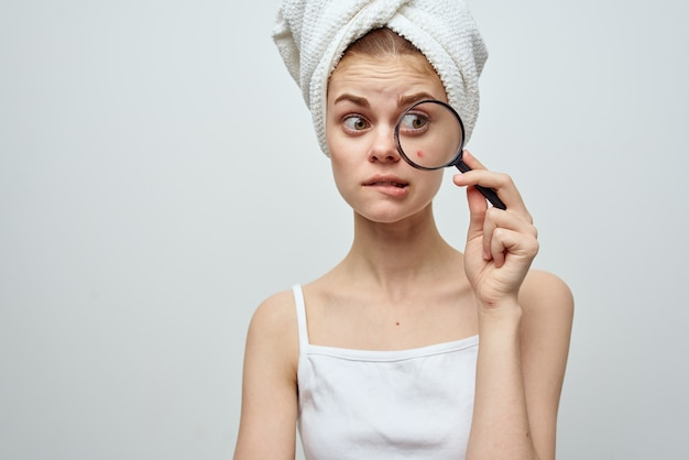 Vrouw met vergrootglas in hand en acne op haar gezicht met een handdoek op haar hoofd