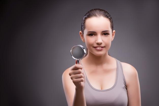 Vrouw met vergrootglas in sportenconcept