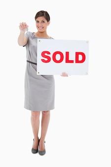 Vrouw met verkocht teken die sleutel overhandigen