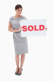 Vrouw met verkocht teken in haar handen