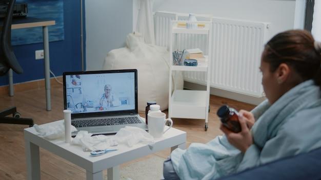 Vrouw met verkoudheid en griep die videogesprek gebruikt voor telegeneeskunde