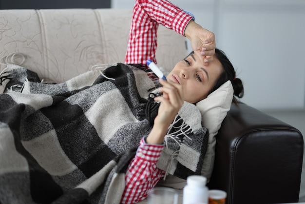 Vrouw met verkoudheid liggend op de bank onder dekens en kijkend naar thermometerisolatie voor ademhaling