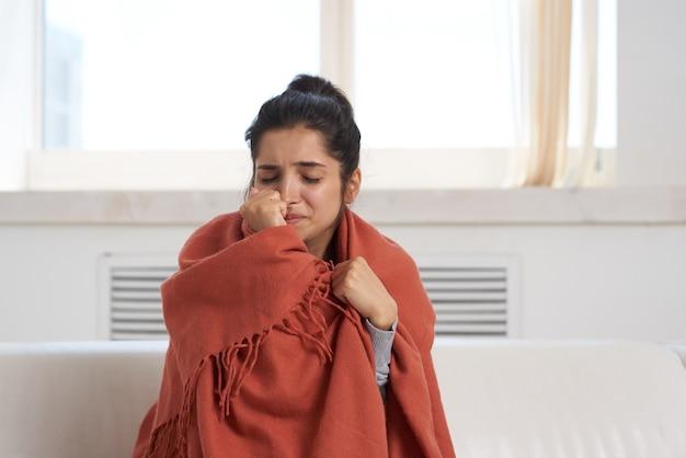 Vrouw met verkoudheid thuis op de bank bedekt met een deken