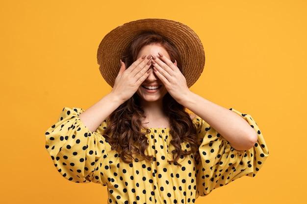 Vrouw met verrassingsgezicht benadeelt haar ogen met haar handen. het dragen van strohoed en stijlvolle zomerjurk.