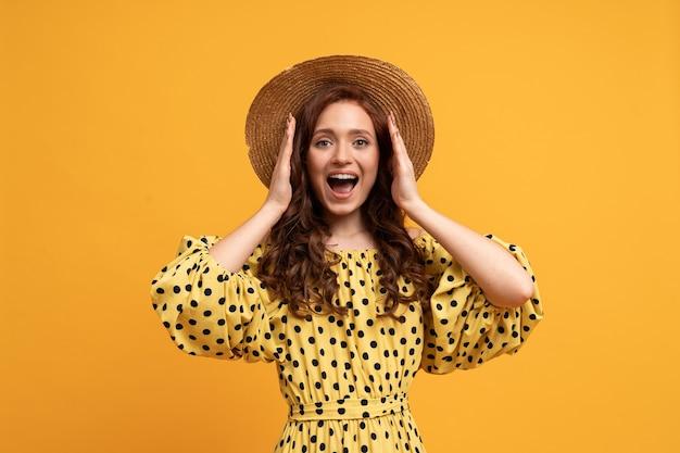 Vrouw met verrassingsgezicht benadeelt haar oren met haar handen. het dragen van strohoed en stijlvolle zomerjurk.