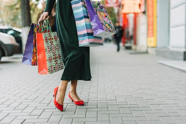 Vrouw met verschillende gekleurde pakketten op straat bijsnijden