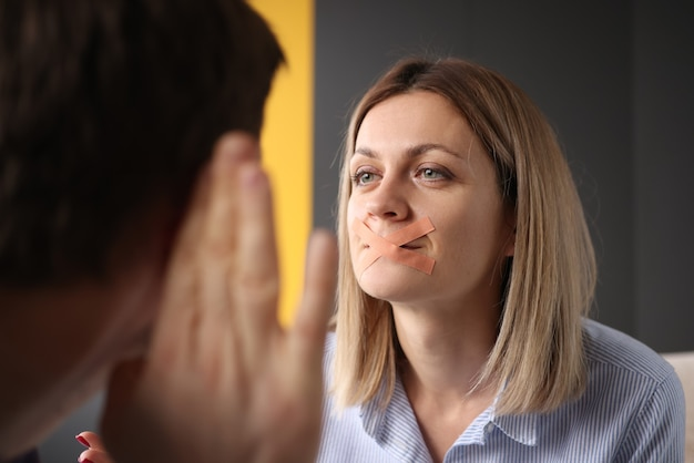 Vrouw met verzegelde mond probeert iets tegen de mens te zeggen. stilte en misverstanden in het concept van familierelaties Premium Foto