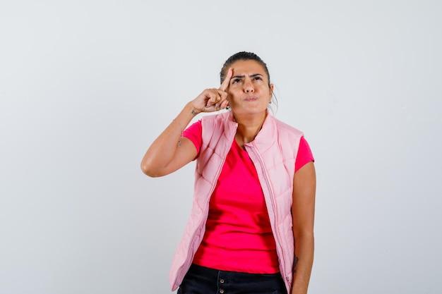 Vrouw met vinger op gezicht in t-shirt, vest en peinzend kijkend