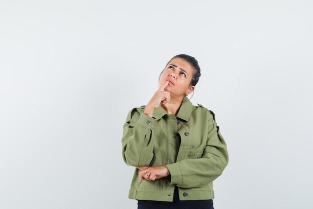 Vrouw met vinger op kin in jas, t-shirt en peinzend op zoek