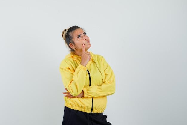 Vrouw met vinger op wang in sport pak en peinzend, vooraanzicht op zoek.