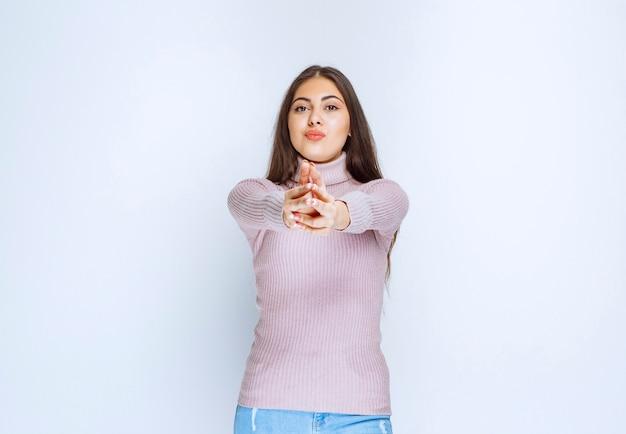 Vrouw met vingerpistool teken als een crimineel.