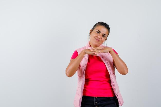 Vrouw met vingers geklemd in t-shirt, vest en hoopvol