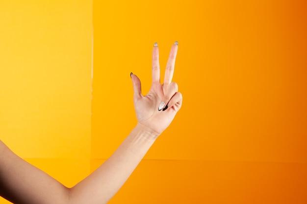Vrouw met vingers toont drie op oranje achtergrond